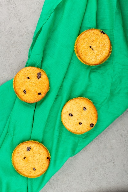 Draufsicht kuchen rund lecker auf dem grünen gewebe und grau Kostenlose Fotos