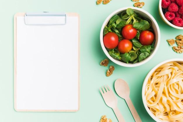 Draufsicht lebensmittelbehälter mit himbeeren, salat und nudeln mit leerer zwischenablage Kostenlose Fotos