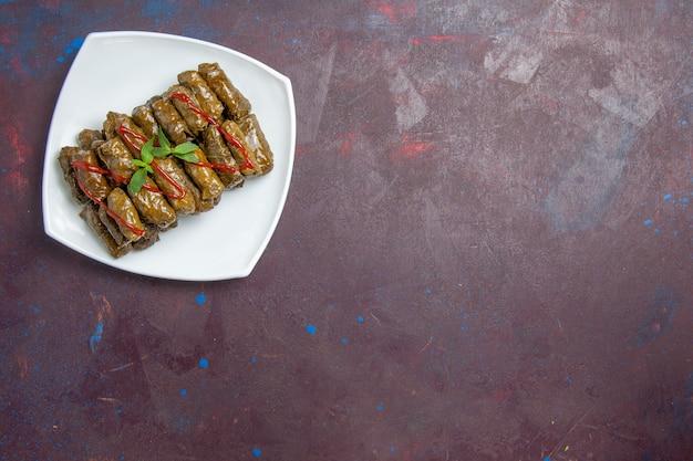 Draufsicht leckere blatt-dolma-hackfleischschale innerhalb der platte auf der dunkelheit Kostenlose Fotos