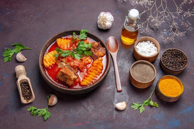 Draufsicht leckere fleischsauce suppe mit verschiedenen gewürzen auf schwarzer bodensauce suppe essen abendessen Kostenlose Fotos