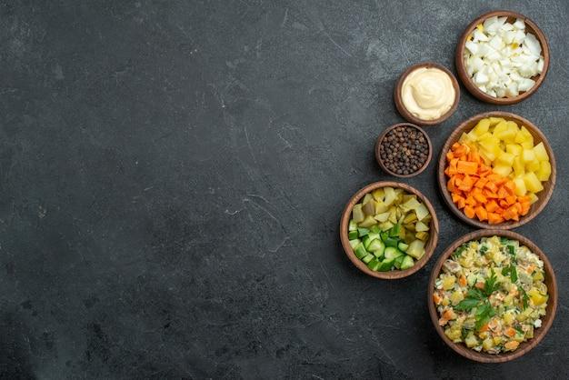 Draufsicht leckeren mayonaonaise-salat mit geschnittenem frischem gemüse auf schwarz Kostenlose Fotos