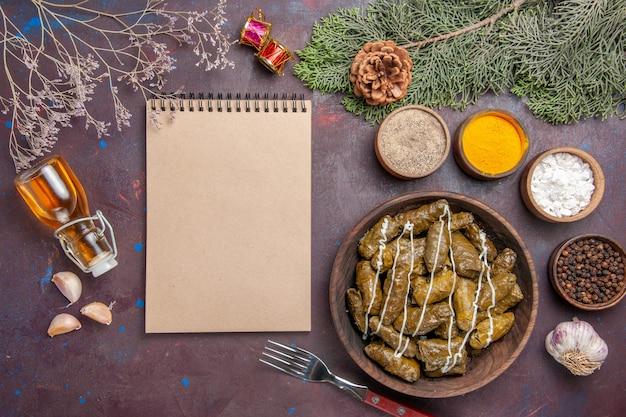 Draufsicht leckeres blatt dolma fleischgericht mit gewürzen auf dunklem schreibtisch Kostenlose Fotos