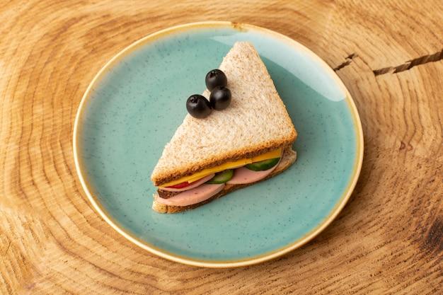 Draufsicht leckeres sandwich mit olivenschinken-tomatengemüse innerhalb platte auf dem hölzernen hintergrundsandwich-nahrungsmittelsnackfrühstück Kostenlose Fotos