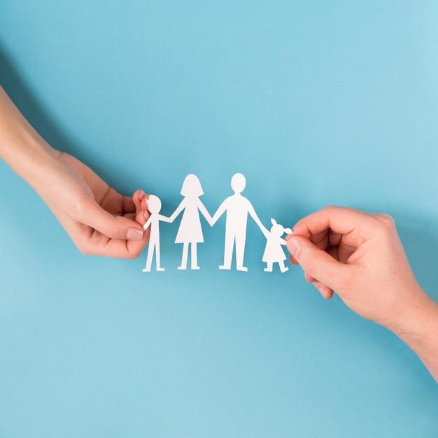Draufsicht leute, die in händen niedliche papierfamilie halten Kostenlose Fotos
