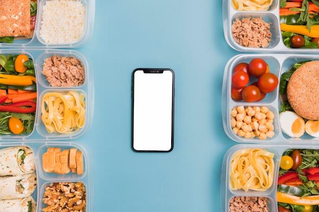 Draufsicht lunchboxen mit leerem telefon Kostenlose Fotos