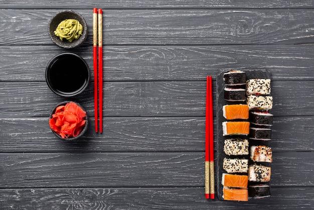 Draufsicht maki sushizusammenstellung auf schiefer mit essstäbchen Kostenlose Fotos