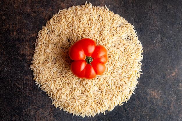 Draufsicht makkaroni in einer kreisform mit tomate auf ihnen auf dunklem strukturiertem hintergrund. horizontal Kostenlose Fotos