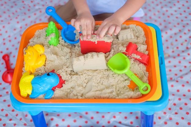 Draufsicht nah oben vom kleinen asiat 2 jahre alten kleinkindjungen, der zu hause mit kinetischem sand spielt Premium Fotos