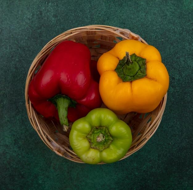 Draufsicht-paprika in einem korb auf grünem hintergrund Kostenlose Fotos