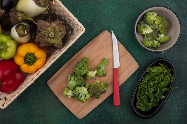 Draufsicht paprika mit auberginen in einem korb mit brokkoli auf einem schneidebrett mit einem messer auf einem grünen hintergrund Kostenlose Fotos