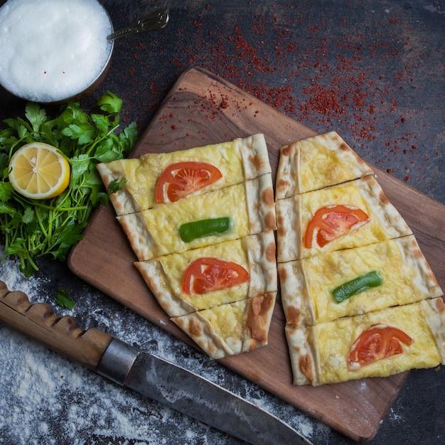 Draufsicht pide mit käse und petersilie und zitrone und ayran im schneidebrett Kostenlose Fotos