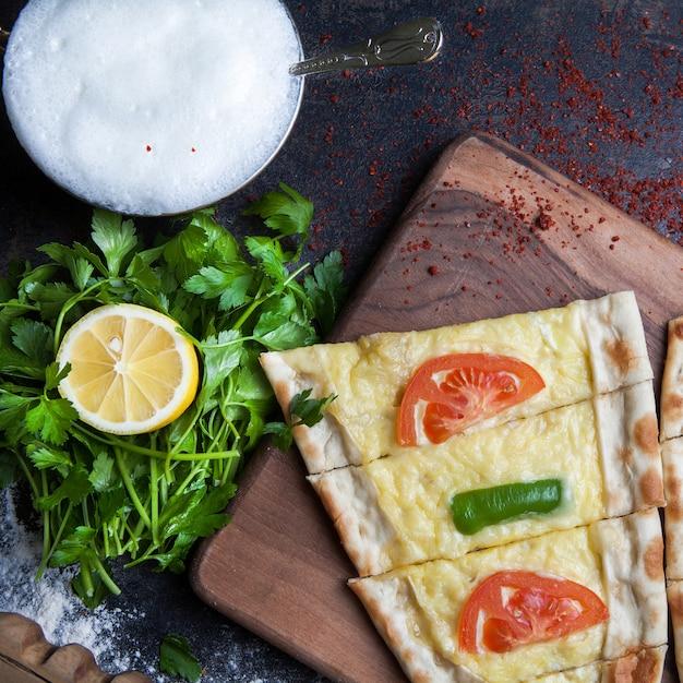 Draufsicht pide mit petersilie und zitrone und käse und ayran im schneidebrett Kostenlose Fotos