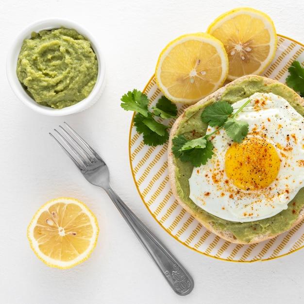 Draufsicht pita mit avocadoaufstrich und spiegelei auf teller mit gabel Kostenlose Fotos