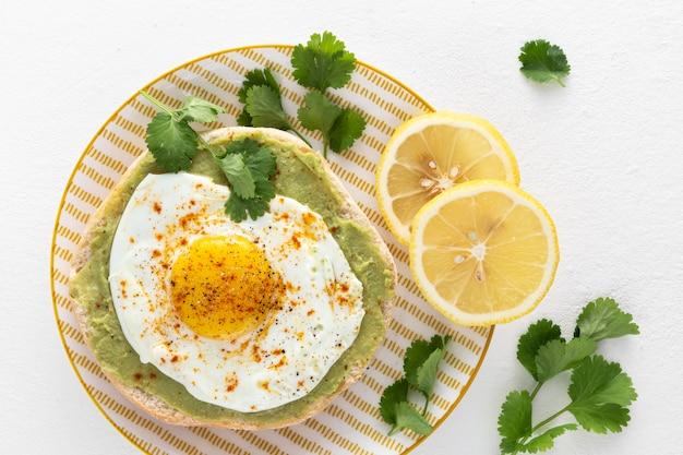 Draufsicht pita mit avocadoaufstrich und spiegelei mit zitronenscheiben Kostenlose Fotos