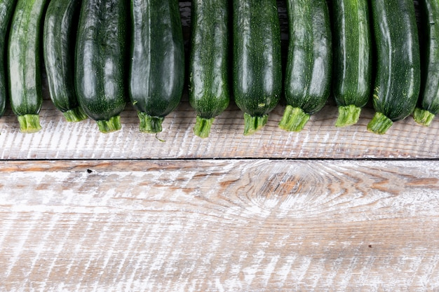 Draufsicht reihte frische zucchini auf hellem holztisch an. Kostenlose Fotos