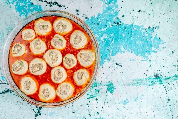 Draufsicht rohe fleischige teigteigscheiben mit hackfleisch innen mit tomatensauce innen glas Kostenlose Fotos