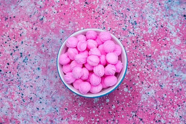Draufsicht rosa bonbons innerhalb platte auf dem bunten hintergrund süßigkeiten zucker goody farbe Kostenlose Fotos