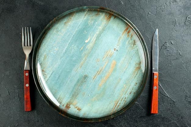Draufsicht rundes plattenmesser und eine gabel auf dunkler oberfläche Kostenlose Fotos