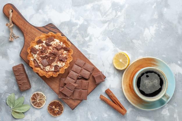 Draufsicht sahne kleiner kuchen mit schokoriegeln und tee auf dem hellen schreibtisch süßer kuchen zuckercreme schokolade Kostenlose Fotos