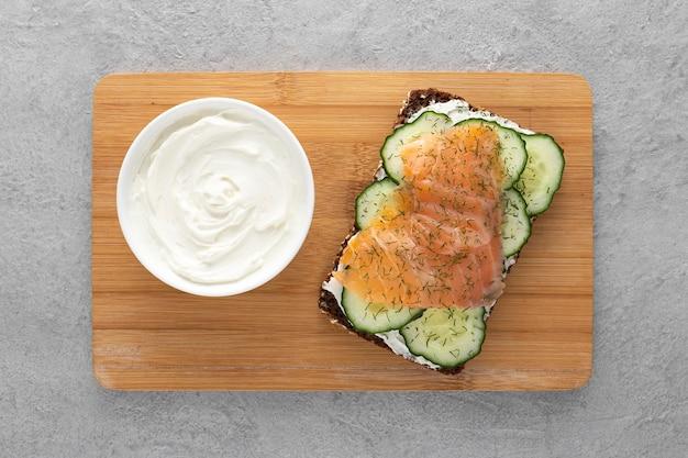 Draufsicht-sandwich mit gurken und lachs auf schneidebrett Kostenlose Fotos