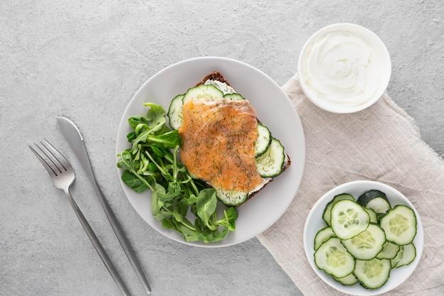 Draufsicht-sandwich mit gurken und lachs auf teller mit besteck Kostenlose Fotos