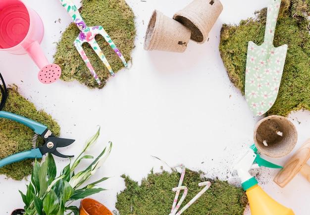 Draufsicht schaufel; gartengabel; gartenschere; gießkanne; rasen; sprühflasche auf weißem hintergrund Kostenlose Fotos