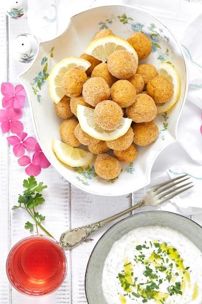 Draufsicht schoss von der platte mit falafel und dip-sauce mit joghurt, tahine und petersilie. Premium Fotos