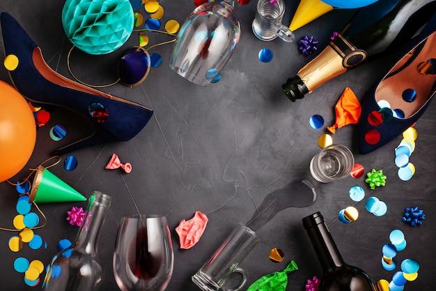 Draufsicht schoss von nach einer parteifeier mit leeren flaschen, weinglas, mädchenschuhen und parteizubehör Premium Fotos