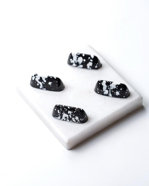 Draufsicht schwarz im weißen fleck praline auf weißem stand Kostenlose Fotos