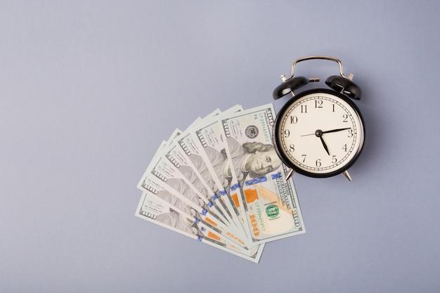 Draufsicht schwarzer metallwecker auf einem stapel von dollarbanknoten. flach legen Premium Fotos