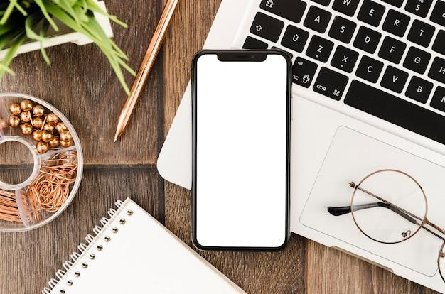 Draufsicht smartphone-vorlage über arbeitsbereich Premium Fotos