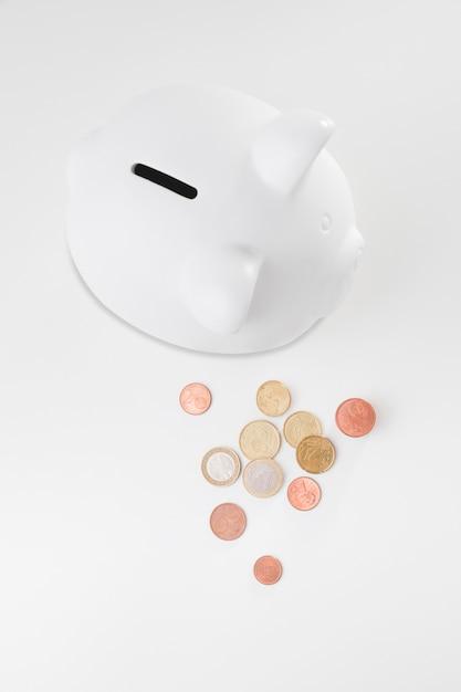 Draufsicht sparschwein mit münzen daneben Kostenlose Fotos