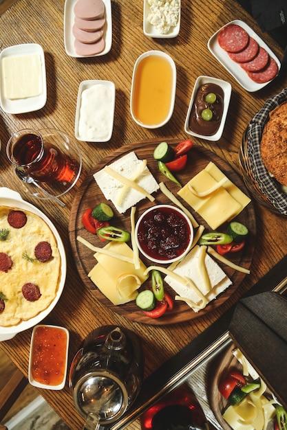 Draufsicht stellte frühstückskäse-wurstmarmelade-honig-sauerrahmgemüse mit rührei und tee auf den tisch Kostenlose Fotos