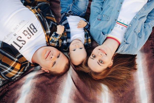 Draufsicht stockfoto der glücklichen jungen familie von mutter, vater und kleinkindsohn lächelnd an der kamera, die auf bett liegt. Premium Fotos
