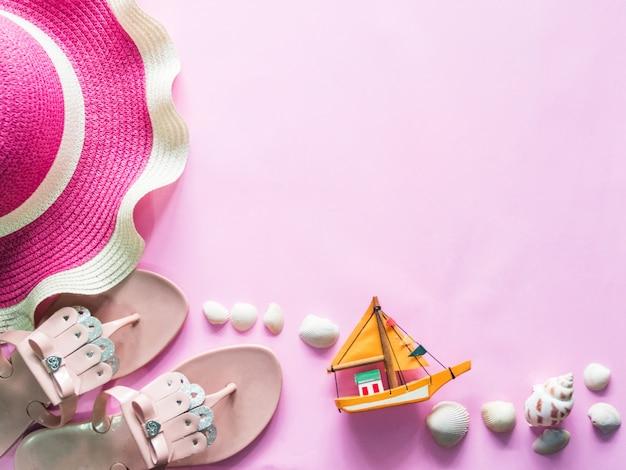 Draufsicht: strandzubehör auf rosa hintergrund. Premium Fotos