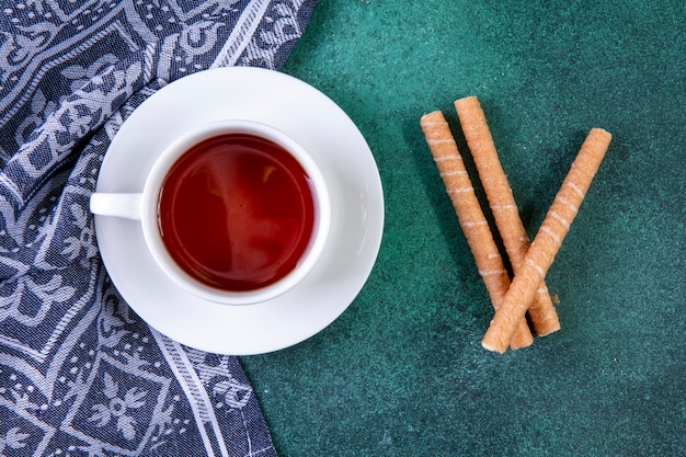 Draufsicht süße röhren mit einer tasse tee auf grün Kostenlose Fotos