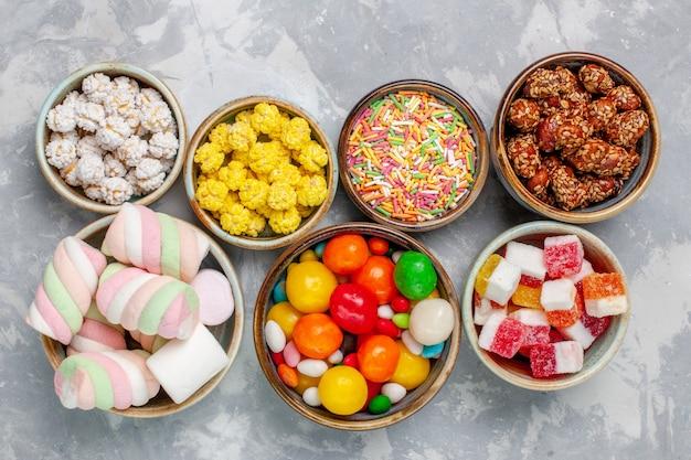 Draufsicht-süßigkeitszusammensetzung verschiedenfarbige bonbons mit marshmallow in töpfen auf weißem schreibtischzuckerbonbonbonbon süßes möbel Kostenlose Fotos