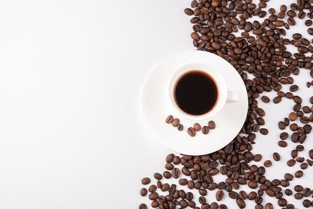 Draufsicht tasse kaffee mit gerösteten bohnen Kostenlose Fotos