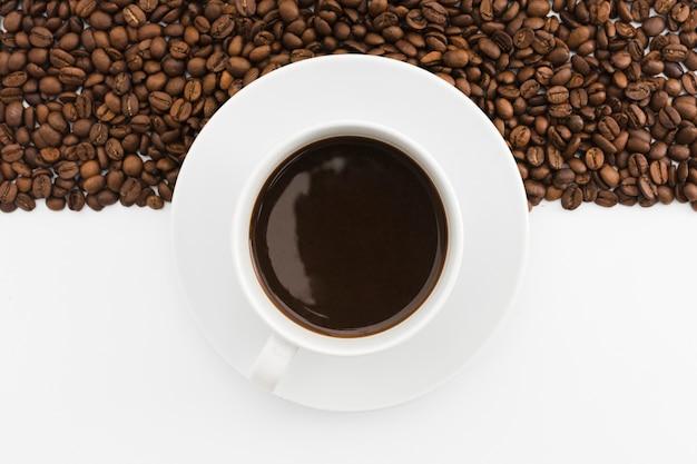 Draufsicht tasse kaffee mit gerösteten bohnen Premium Fotos