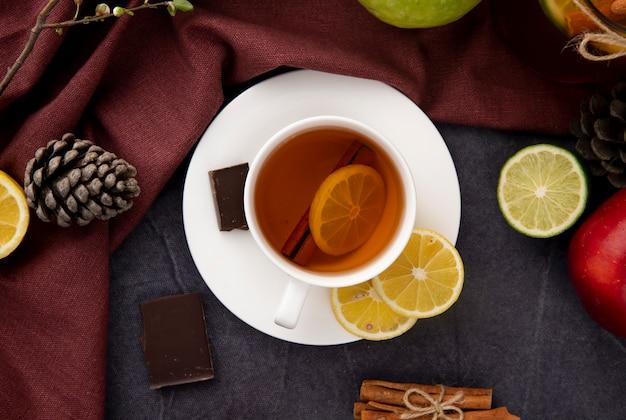 Draufsicht tasse schwarzen tee mit scheibe zitronenzimt dunkle schokolade äpfel tannenzapfen und limettenscheibe Kostenlose Fotos