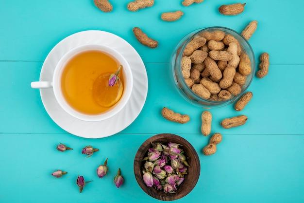 Draufsicht tasse tee mit einer scheibe zitrone und erdnüssen auf einem hellblauen hintergrund Kostenlose Fotos