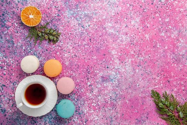 Draufsicht tasse tee mit französischen macarons auf rosa oberfläche Kostenlose Fotos