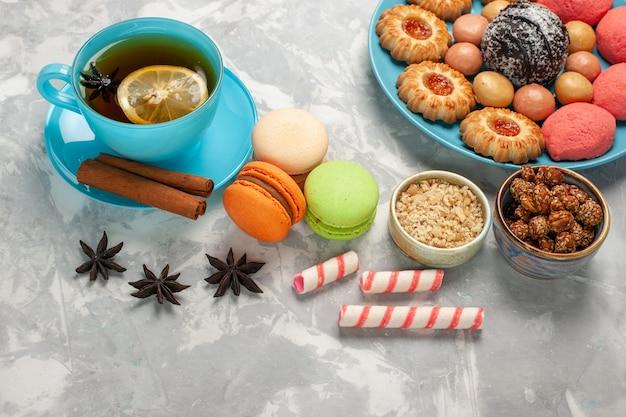 Draufsicht tasse tee mit französischen macarons keksen und kuchen auf weißer oberfläche Kostenlose Fotos