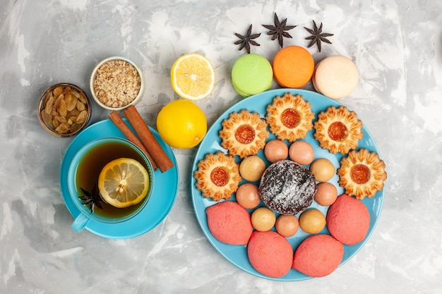 Draufsicht tasse tee mit französischen macarons zuckerkeksen und kuchen auf weißer oberfläche Kostenlose Fotos
