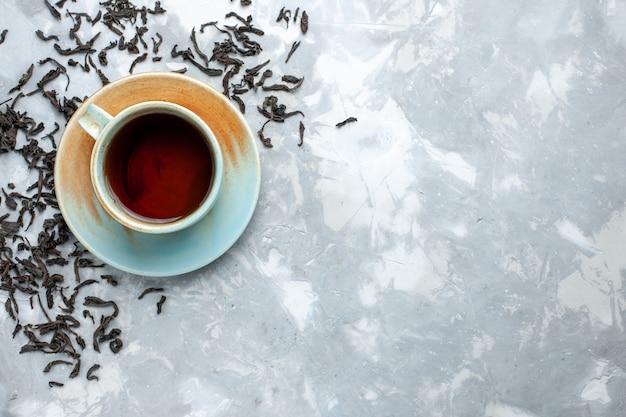 Draufsicht tasse tee mit frischen getrockneten teekörnern auf dem leuchttisch, teegetränk frühstück Kostenlose Fotos