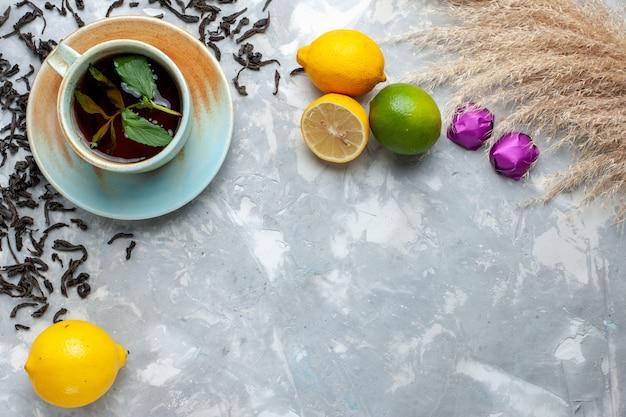 Draufsicht tasse tee mit frischen getrockneten teekörnern bonbons und zitrone auf dem leuchttisch, teegetränk frühstück Kostenlose Fotos