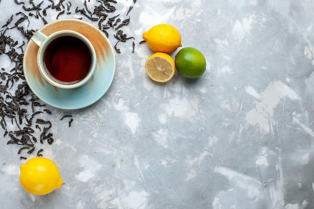 Draufsicht tasse tee mit frischen getrockneten teekörnern und zitrone auf dem leuchttisch, teegetränk frühstück Kostenlose Fotos