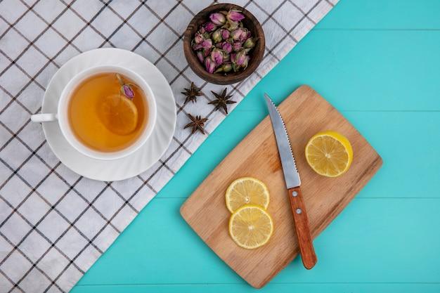 Draufsicht tasse tee mit geschnittener zitrone auf einem brett mit einem messer mit getrockneten blumen auf einem hellblauen hintergrund Kostenlose Fotos