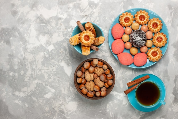 Draufsicht tasse tee mit kekskuchen und nüssen auf weißer oberfläche Kostenlose Fotos
