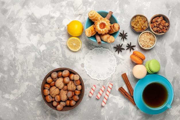 Draufsicht tasse tee mit kuchen und nüssen auf weißer oberfläche Kostenlose Fotos